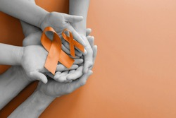 Adult and child hands holding orange Ribbons,  Leukemia cancer and Multiple sclerosis, COPD and ADHD awareness, world kidney day