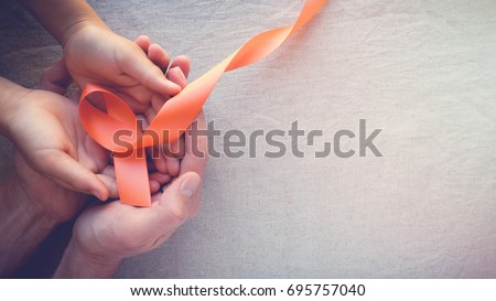 Adult and child hands holding orange Ribbons,  Leukemia cancer awareness and Multiple sclerosis awareness, COPD and ADHD awareness