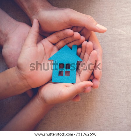 Adult and child hands holding paper house, family home, homeless housing and home protecting insurance concept, international day of families, foster home care, family day care, social distancing