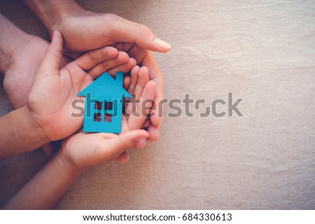 Adult and child hands holding paper house, family home, homeless housing and real estate, insurance concept