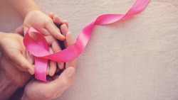 Adult and child hands holding pink ribbons, Breast cancer awareness, abdominal cancer awareness and October Pink day panoramic background , world cancer day