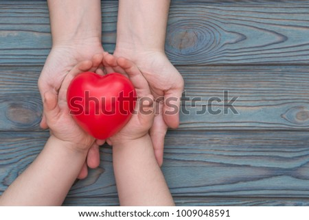 adult and child hands holding red heart, health care, insurance and family concept, world heart day #1009048591