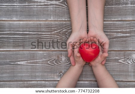 adult and child hands holding red heart, health care, insurance and family concept, world heart day #774732208