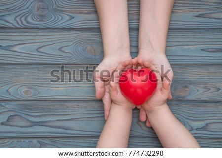 adult and child hands holding red heart, health care, insurance and family concept, world heart day #774732298