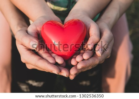 adult and child hands holding red heart, health care love, give, hope and family concept, #1302536350