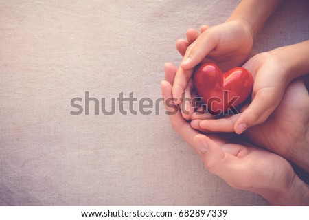 adult and child hands holding red heart, health care, love, hope and family concept