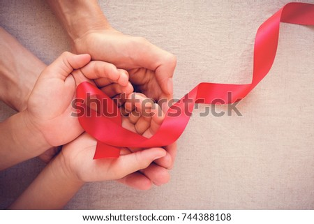 adult and child hands holding red ribbon, hiv awareness concept, world AIDS day