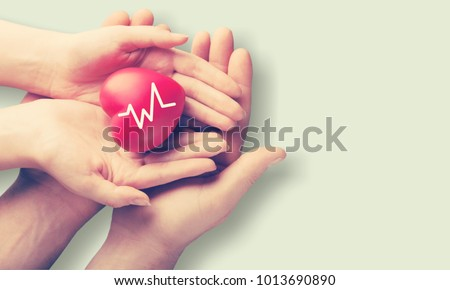 Adult and child hands holiding red heart