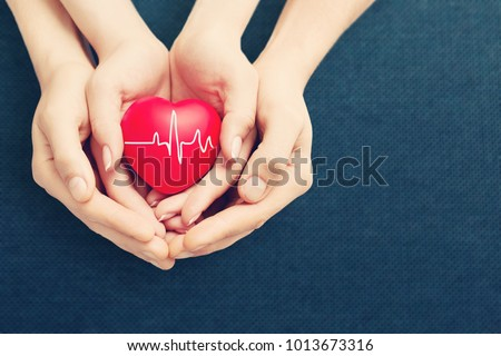 adult and child holiding red heart