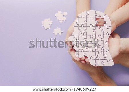 Adult and children hands holding brain with puzzle paper cutout, autism, memory loss, dementia, epilepsy and alzheimer awareness, world mental health day, world Parkinson day concept
