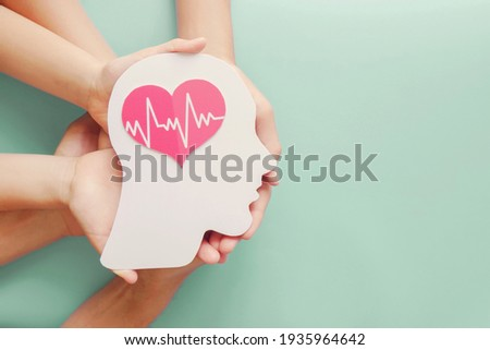 Adult and children hands holding paper brain and heart, brain stroke, world heart day, world mental health day, Alzheimer and wellness concept