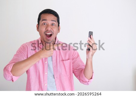 Adult Asian man showing excited face expression when pointing his finger to moblie phone Foto stock ©