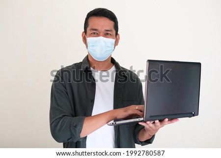 Adult Asian man wearing protective mask holding a laptop. Working from home concept Zdjęcia stock ©