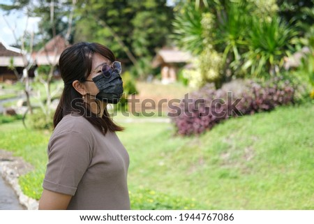 Adult Asian women wearing black medical mask while enjoying fresh air in the garden Stok fotoğraf ©