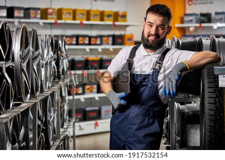 adult auto mechanic man in uniform have rest after hard working day, standing by rack of car wheels. auto, car, transport concept