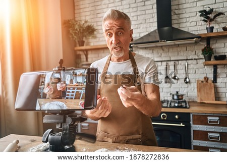 Adult bearded chef standing on the kitchen while filming himself for blog. Mature man explaining a recipe for baking a pie and holding berries in hands while looking at the phone camera. Live stream Stock photo ©