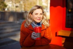 Adult blond female in red outerwear smiling and looking at camera while sitting at table and enjoying takeaway beverage in street cafeteria