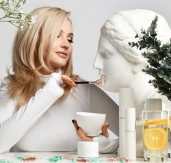 Adult blonde good looking woman with healthy skin sits at table with set of cosmetics means applying statue head facial mask with brush. Beautiful woman, hair and skincare style concept, fashion