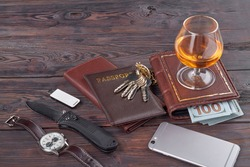 Adult businessman accessories top view. Passport with keys and glass of whiskey on brown wooden table.