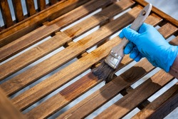 Adult carpenter craftsman painting with water-based paint the strips of a chair wooden garden. Housework, do it yourself.