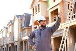 Adult caucasian foreman and architect giving indication on construction site and wearinhg hardhat, brick building in backgound. Concept of builder profession and working abroad in Canada.
