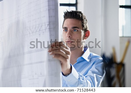 adult caucasian male architect examining blueprints. Horizontal shape, head and shoulders, side view