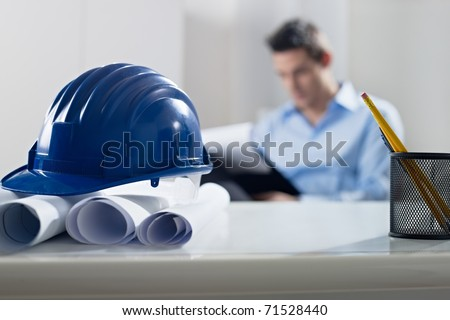 adult caucasian male architect examining documents. Focus on blueprints and hardhat in foreground. Horizontal shape, front view
