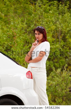 Adult caucasian woman standing by the white car.