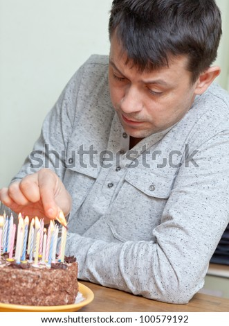 Adult celebrates his birthday. Man lighting the candles