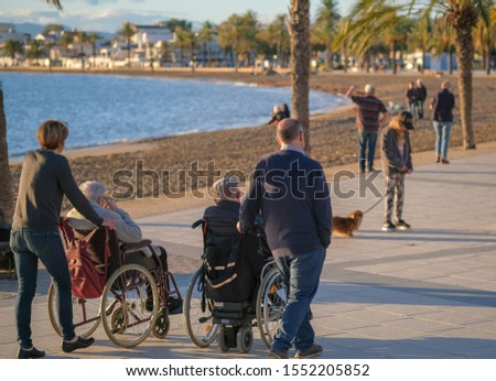 Adult children spend time with their parents with disabilities in wheelchairs on blue sea. Family walks along the promenade on a sunny day. A wheelchair is being pushed by the accompanying people.  #1552205852