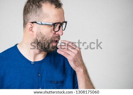 Adult clever guy wearing eyeglasses and blue shirt having thinking, focused face expression. Man focusing on his work, contemplating idea. #1308175060