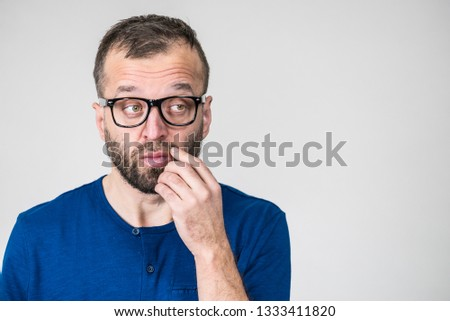 Adult clever guy wearing eyeglasses and blue shirt having thinking, focused face expression. Man focusing on his work, contemplating idea. #1333411820