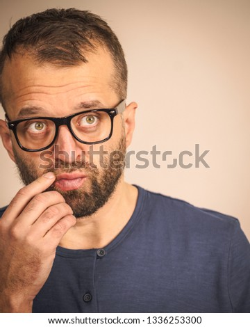 Adult clever guy wearing eyeglasses and blue shirt having thinking, focused face expression. Man focusing on his work, contemplating idea. #1336253300