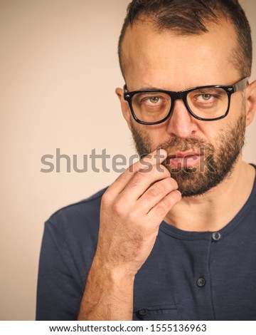 Adult clever guy wearing eyeglasses and blue shirt having thinking, focused face expression. Man focusing on his work, contemplating idea.