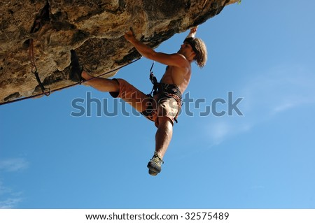 Adult climbing hard overhanging rock.