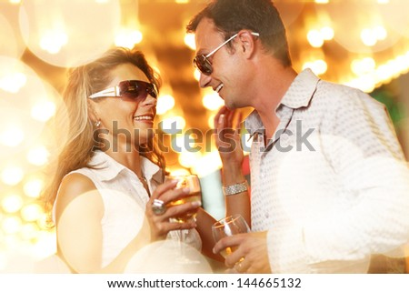 Adult couple enjoying nightlife with glasses of champagne. Shallow DOF. #144665132