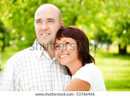 adult couple of husband and wife in park, both smiling and looking away from camera