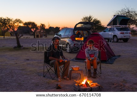 Adult couple relaxing in camping site by night. Adventure in National Park, South Africa. Burning camp fire and tent in the background. Toned image.