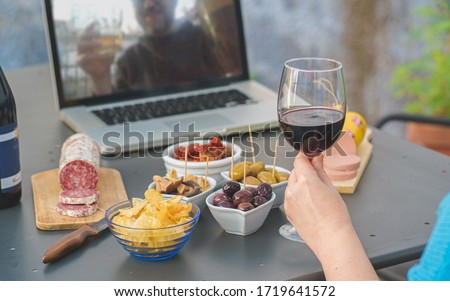Adult couples clinking online with beer and wine making a quarantine happy hour toast via internet video call. Alcohol and aperitif lifestyle concept. focus on the wineglass.