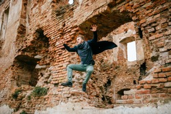 Adult crazy angry unusual excited male portrait. Businessman in flight motion. Young boy with funny comic expressive odd face emotions jumping from brick wall. Flying person. Sport activity outdoor