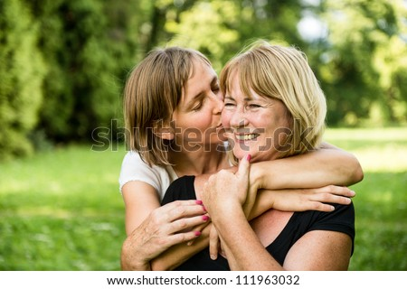 Adult daughter kissing her smiling happy senior mother - outdoor in nature