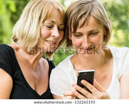 Adult daughter showing on smartphone to her mature mother outdoor in nature