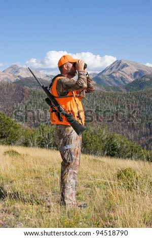 adult deer hunter looking through binoculars