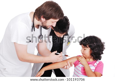 Adult doctor giving injection to young female patient while student is watching