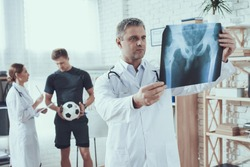 Adult doctor looking at an x ray of an injured athlete. Sportsman in the background holds the ball and speaks to the woman by the doctor.