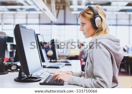 adult education, student in headphones working on computer in the library or classroom of university