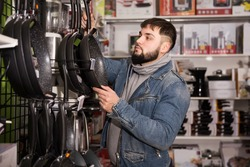 Adult efficient friendly male is looking on new frying pan in hardware shop