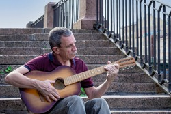 Adult elderly man of retirement age plays old six-string classical acoustic guitar outdoors while sitting on granite staircase on summer evening in city. Hobby, doing what you love. Selective focus.