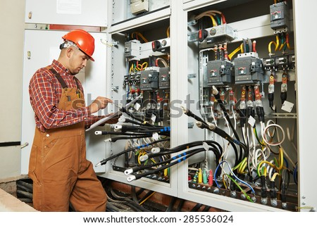 adult electrician builder engineer worker with electric scheme plan in front of fuse switch board #285536024