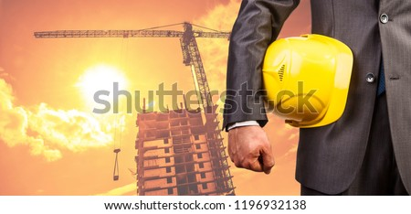 adult engineer or inspector hand holding yellow plastic helmet for workers security over highrise buildings construction cranes on background evening sunset sky Crane lifts load background.No face